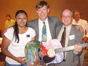 Mayor John Hickenlooper poses with Veronica Solis, the artist who painted Hickenlooper's personal guitar, and Board Member Ted Bright who was the high bidder on the guitar