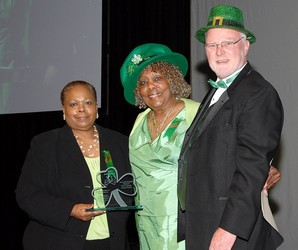 Barbara Shannon-Banister (center) accepts Volunteer of the Year award from MCPN President/CEO David Myers and City Council Member Deborah Wallace.