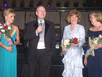Cancer League President Dave Weisberg presents flowers to Gala chairs Jane Hampe (left), Barbara Reece and Kaye Music