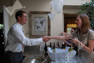 Board member Steve Hart accepts some wine from Sara Struckman