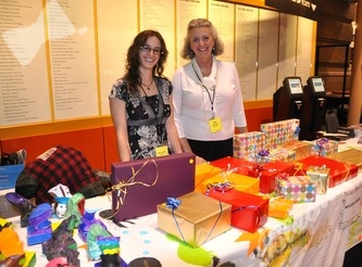 Volunteers Monica Bolles (l) and Mary Carrothers are ready to entice guests with some colorful mystery gifts.