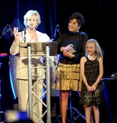 Board President Sue Ellen Goss, left, presents Jody Epstein, with her granddaughter Gabby, with the chairman's award