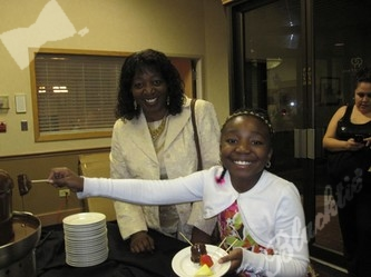 Janell Gotier enjoys watching her daughter, Nyna Moore dip into the never ending chocolate flow