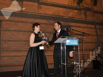 Executive Director Karla Johnson-Grimes receives a bouquet of flowers from President Marc Cutilletta in recognition for her committed efforts to ArtReach