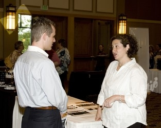 Rebecca Saltman (right) of Foot in the Door Productions talks with a guest of the fair.