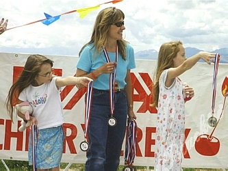 Mom Colleen Schneckenburg hands out medals with her daughters, Nicole and Crystal. Colleen's husband was the 27th highest fundraiser in 2003 and has been riding in the Courage Classic since 1993.