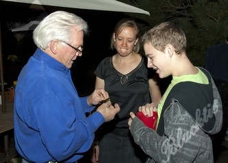 Camper Henry Gray pins a sheriff's badge onto an auction winner.